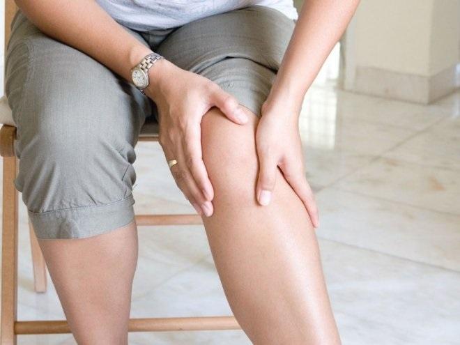 Женщина с больными ногами сидит на стуле